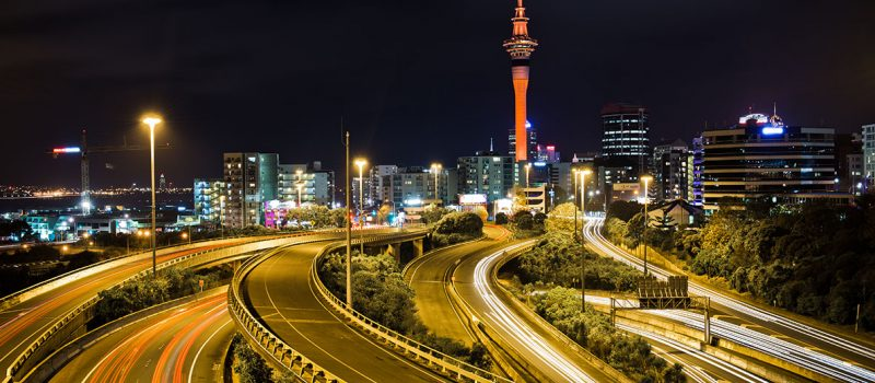 Busy Auckland city by night with the Sky Tower